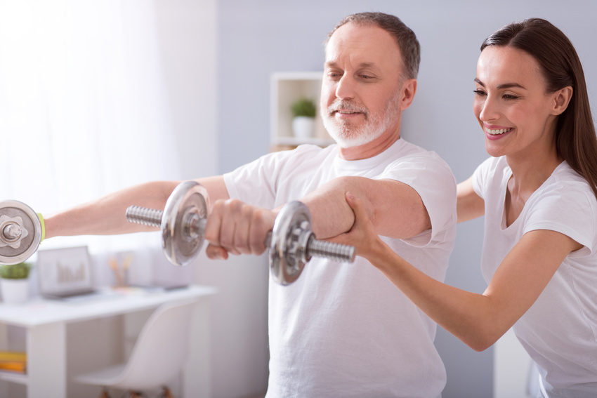 Using dumbbells. Cheerful male patient with dumbbells during physical therapy praxis and merry female physiotherapist helping him